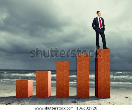 Business person on a graph, representing success and growth - stock photo