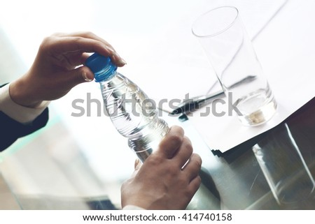 Business person opens a bottle of fresh water at desk - stock photo