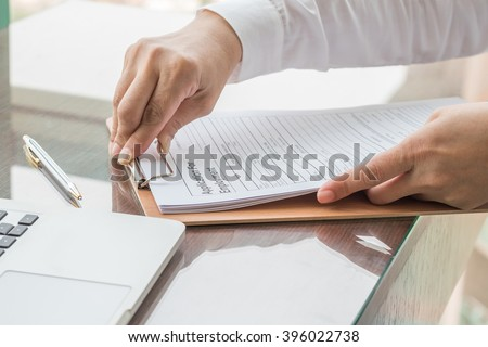 Business person's women hand filing blank application for employment form paper on working office table desk: Fill in empty document template applying for profession job career human resources