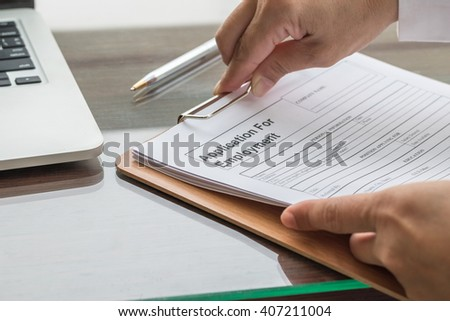 Business person's women hand filing blank application for employment form paper on working office table desk: Fill in empty document template applying for profession job career human resources - stock photo