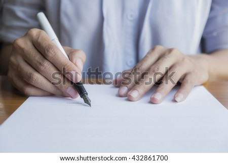 Business person Signing Contract, Women writing paper at the desk, man writing with pen and reading books at table, man Signing, Contract, Form. in office ,morning light. Business concept.  - stock photo