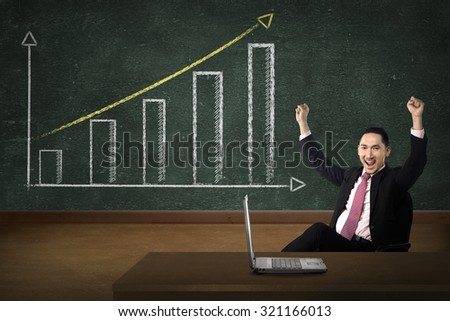 Business person smile over increasing graph drawing on chalk board