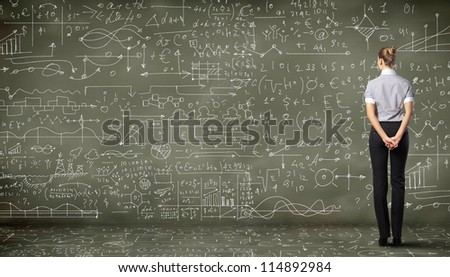Business person standing against the blackboard with a lot of data written on it - stock photo