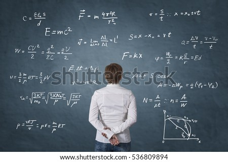 Business person standing in front of mathematical formula. Science concept.