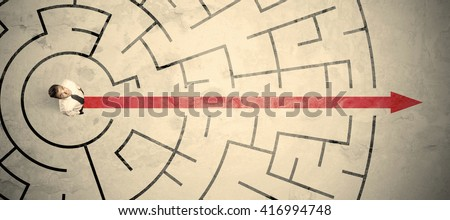 Business person standing in the middle of a circular maze with red arrow - stock photo