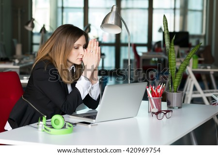 Business Person thinking hard in blessing hands Gesture at grey Desk with Computer and other Electronics in contemporary digital corporate Office Interior - stock photo