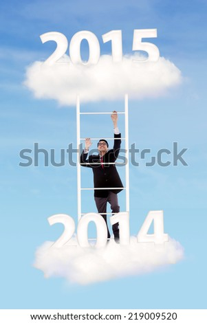 Business person trying to climb upward on ladder over cloud with number 2014-2015