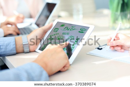 Business person using a touch screen device with ecological  - stock photo