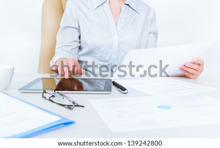 Business person wearing in casual shirt sitting at desk and check documents with the help of digital tablet in the office - stock photo