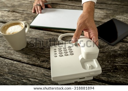 Business person with blank paper and cup of fresh coffee in front of him about to make a phone call in a customer support and telemarketing concept. - stock photo