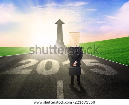 Business person with cardboard head, standing on the road to future 2015
