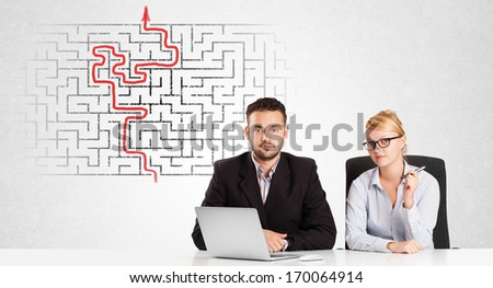 Business persons at desk with labyrinth in the background - stock photo