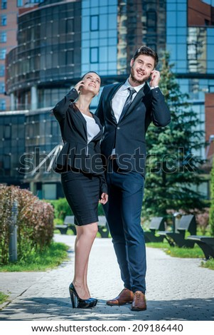 Business phone calls outside the office. Portrait of two confident and successful businessmen. Business couple standing embracing and holding mobile phone. - stock photo