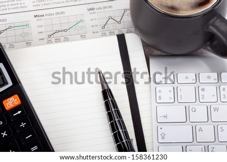 Business photo: coffee with open note, pen, calculator, newspaper (stock index overview) and keyboard - stock photo