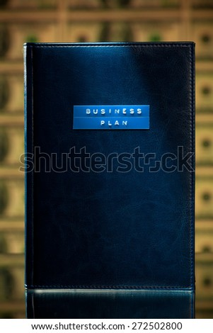 business plan book against money background - stock photo