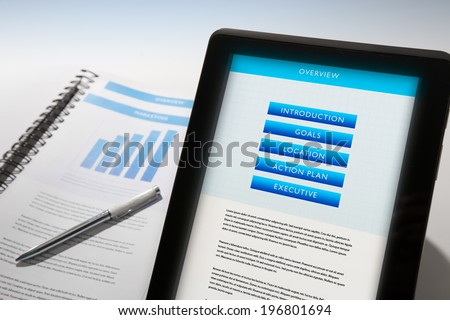 Business Plan displayed on a mobile device and also in binder. - stock photo