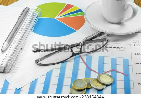 business plan graphics pen cup of coffee glasses planning coins - stock photo