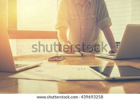 business plan,Man putting his ideas and writing business plan at workplace,and holding pens and papers,making notes in documents, on the table in office,vintage color,morning light ,selective focus.