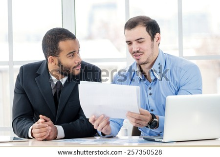 Business plan. Two Confident businessman checking documents while two successful businessman sitting in office at the table in the formal wear. - stock photo