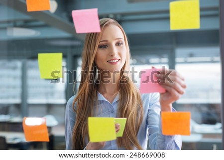 Business plan. Young female professional sticking colourful notes to a glass wall - stock photo