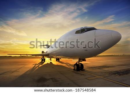 Business plane at sunset - back lit  - stock photo