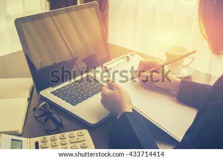 Business planning,Female manager putting his ideas , writing business plan by holding pencil and papers on clip broad making notes in documents on the table in office,vintage color,selective focus.    - stock photo