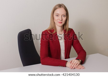 Business portrait of a caucasian blonde woman in red jacket - stock photo