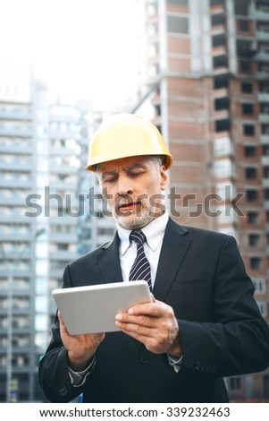 Business portrait of contractor and developer. Aged businessman with helmet standing near his new construction and using tablet computer