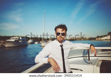 Business portrait of young man in suit posing on a yacht - stock photo