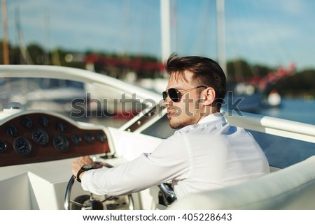 Business portrait of young stylish man in suit and sunglasses driving yacht