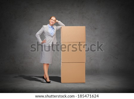 business, post and transportation concept - smiling businesswoman with tower of cardboard boxes