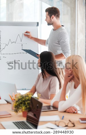 Business presentation. Confident young man standing near whiteboard and sketching while his colleagues sitting at the desk  - stock photo