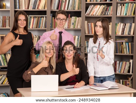 Business presentation on laptop computer. Cheerful business group giving thumbs up. Happy group of friends. Successful business people with thumbs up and smiling. Four women and one man - Students. - stock photo