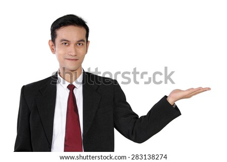 Business presentation with copyspace. Young Asian businessman showing something above his opened hand, isolated on white background
