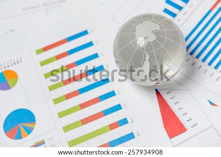 Business presentation with glboe and chart on the desk - stock photo