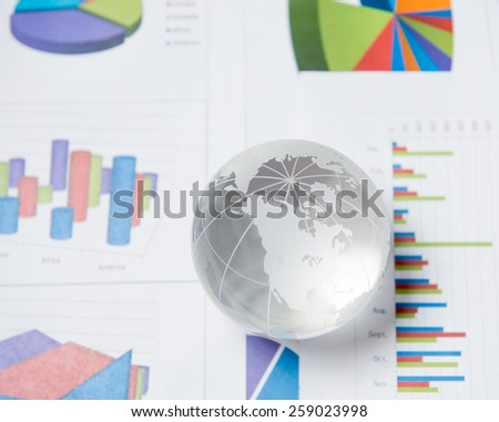 Business presentation with globe and chart on the desk - stock photo