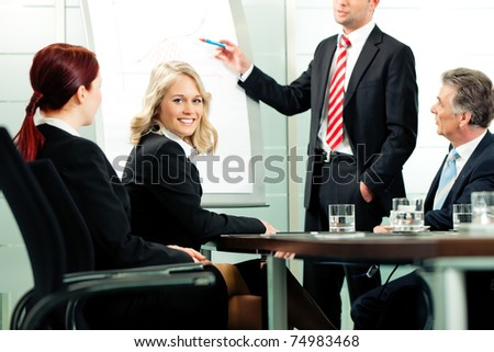 Business - presentation within a team; a colleague is standing on the flipchart - stock photo