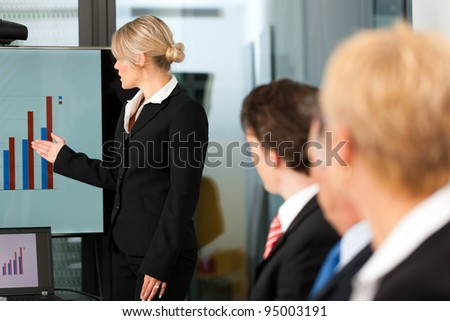 Business - presentation within a team, a female, colleague is standing on the screen - stock photo