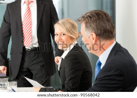 Business - presentation within a team; a male, colleague is standing on the screen - stock photo