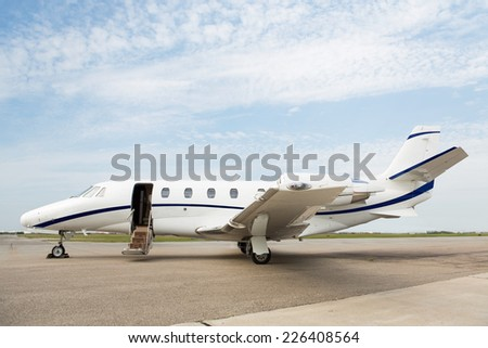 Business private jet parked at terminal - stock photo