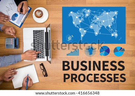 BUSINESS PROCESSES Business team hands at work with financial reports and a laptop - stock photo