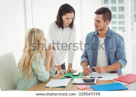 Business professionals discussing at desk in office