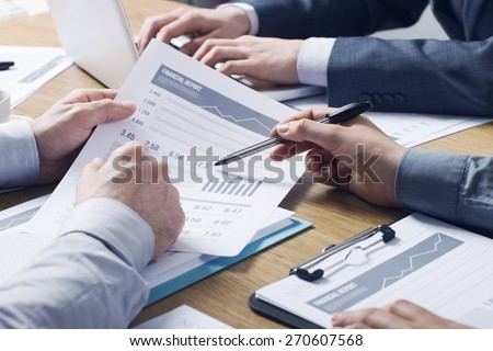 Business professionals working together at office desk, hands close up pointing out financial data on a report - stock photo