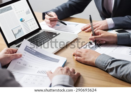 Business professionals working together at office desk, hands close up pointing out financial data on a report, teamwork concept - stock photo