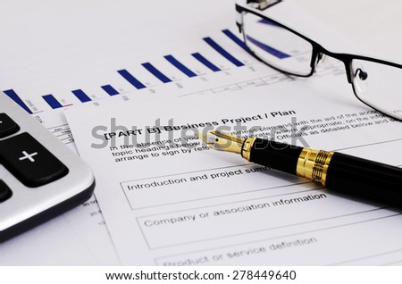 Business project plan with fountain pen and calculator and eyeglasses