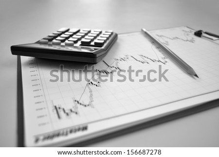Business report containing graphs and charts on a clipboard with a pencil and calculator
