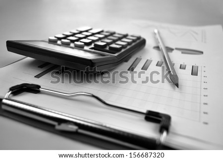Business report containing graphs and charts on a clipboard with a pencil and calculator - stock photo