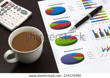 Business report. Cup of coffee on document.