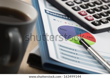 Business report. Cup of coffee on document - stock photo