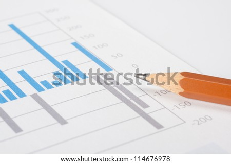 Business report, pencil and graph. Selective focus on pencil lead.